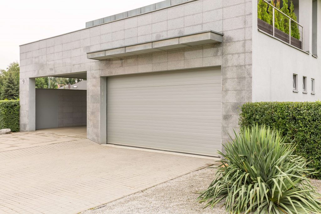 Big grey house with a drive way and a parking garage