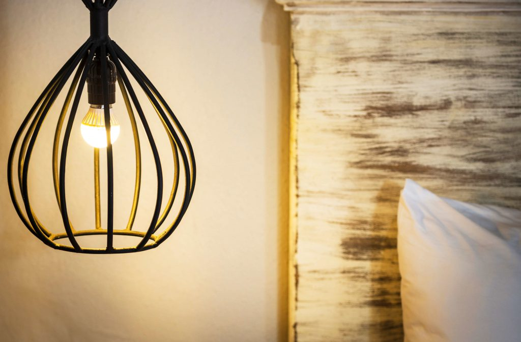 A hanging bedside lamp made from wrought iron