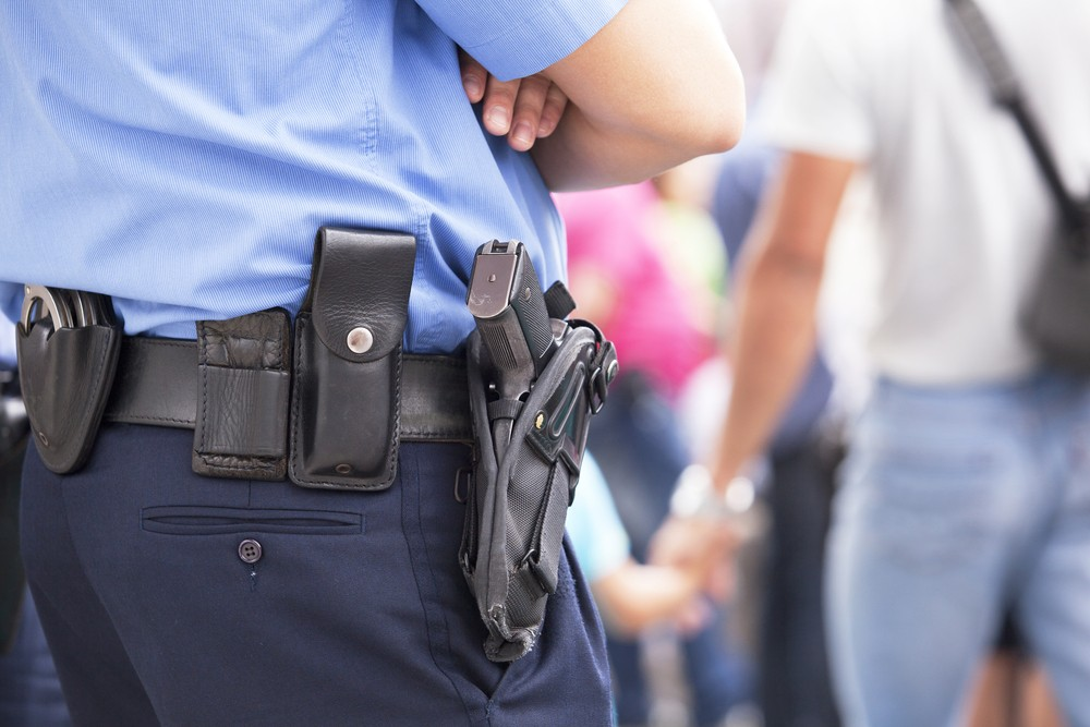 An armed guard can help reduce liability but there is more to consider-- picture of a holstered weapon on a guard's hip