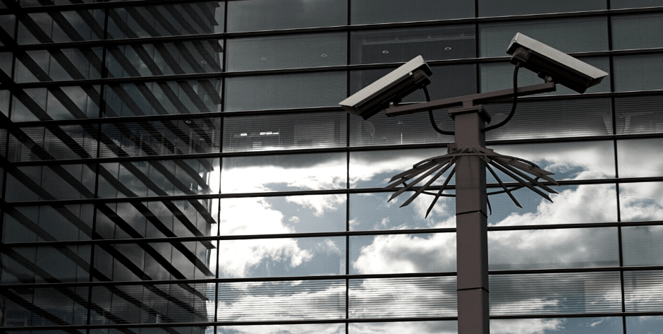 Image of two security cameras on top of a pole in front of a large mirrored building with clouds in the reflection of the mirrors
